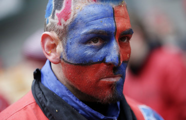 A man with his face painted looks on during an annual carnival battle with oranges in the northern Italian town of Ivrea