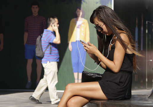 Woman checks her iPhone outside an Apple store in Beijing