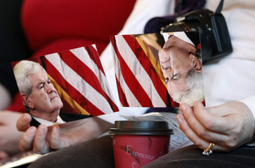Gingrich supporter holds two postcards of Gingrich while listening to him speak at Elly's Tea and Coffee in Muscatine