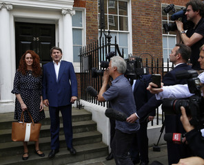 Former News International chief executive Rebekah Brooks and her husband Charlie make a statement to the media in London