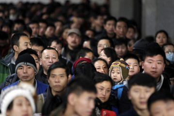 A mother holding her child waits to have their tickets checked among passengers at Beijing Railway Station
