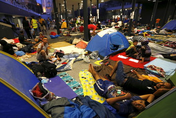 Asylum seekers wait outside a train station in Budapest