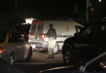 A soldier stands near an ambulance carrying victims of a bomb blast near a military barracks in Nigeria's capital Abuja