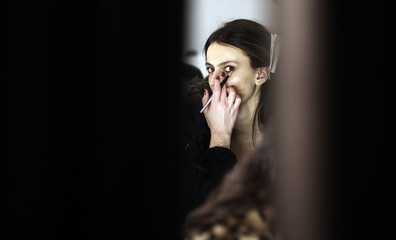 A model prepares backstage for the J. Mendel Fall/Winter 2012 collection show during New York Fashion Week