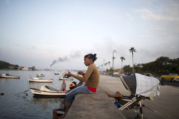 Yanesi Ailan, 23, fishes at the Havana bay's canal as her three year old son sleeps in a baby kart behind her, Havana
