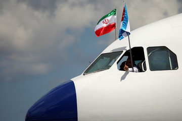 A pilot gestures as Iran and Cuba's flags hang at the cockpit of the airplane carrying Iran's President Hassan Rouhani upon his arrival at Jose Marti International Airport in Havana, Cuba