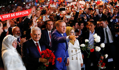 Turkish President Tayyip Erdogan, accompanied by his wife Emine Erdogan and Prime Minister Binali Yildirim with his wife Semiha Yildirim, greet members of his party during the Extraordinary Congress of the ruling AKP in Ankara