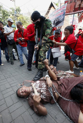 "Thai anti-government ""red shirt"" protesters act out a skit during a rally in Chiang Mai province"