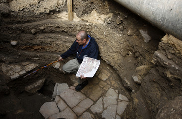 Excavation Director for Israel Antiquities Authority holds a replica of an ancient map in Jerusalem
