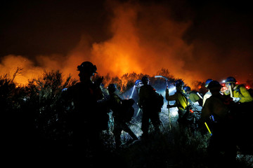 Hotshot firefighters build a fire line after the fire jumped Lytle Creek Road during the Blue Cut fire in San Bernardino County, California