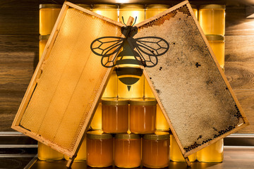 Golden yellow honey glass jar on wooden board Closeup Copy space comp frame empty and filled with bee logo textspace