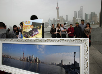 People pose for a family portrait with the Oriental Pearl TV Tower in the background on a hazy day in Shanghai