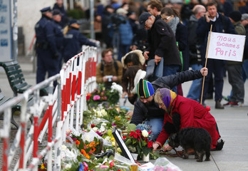 People lay flowers outside the French embassy in Berlin