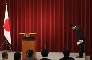 Japan's Prime Minister Kan bows to the Japanese national flag as he leaves a news conference in Tokyo