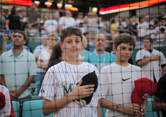 Marlins fan holds hat as national anthem is played on their opening night MLB National League baseball game against Dodgers in Miami