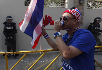 An anti-government protester blows on a noisemaker as he joins others in a march during a rally outside the house of Prime Minister Yingluck Shinawatra during a rally in Bangkok