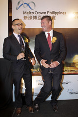 Ho, co-chairman and CEO of Melco Crown Entertainment, laughs with Packer, Australian gambling tycoon and co-chairman of Melco Crown Entertainment, as they pose for a picture during signing deal with local partner Belle Corp in Manila