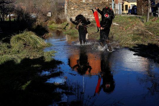 """A man wearing a """"El Diablo"""" (The Devil) mask crosses the Becerril river during the """"Los Carochos"""" winter masquerade in Riofrio de Aliste, Spain"""
