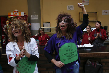 "Cafeteria workers look at demonstrators dressed as zombies as they celebrate after dancing to the music of Michael Jackson's ""Thriller"" song during a protest at the faculty of Political Science at Madrid's Complutense University"