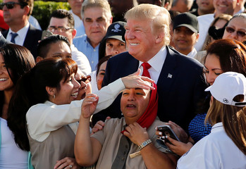 Employee of Republican U.S. presidential nominee Donald Trump plays with his tie as he poses for photos after a campaign event with his them at his Trump National Doral golf club in Miami