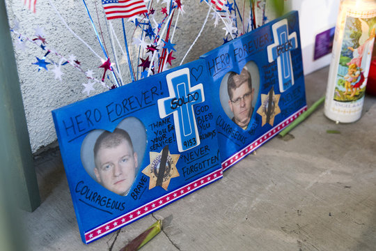 Photos of Metro Police officers Igor Soldo and Alyn Beck are shown at a memorial in front of CiCi's Pizza in Las Vegas
