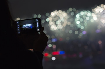 A woman takes pictures during fireworks over Victoria Harbour celebrating the Lunar New Year in Hong Kong