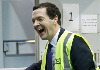 Britain's Chancellor of the Exchequer George Osborne laughs as he works on a production line of decorative panels at a factory in Stockton-on-Tees