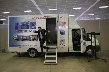 A real estate vendor jumps out of a van during a property fair in Madrid