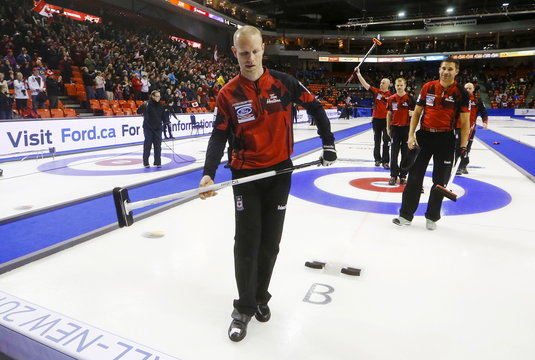 Canada's skip Simmons leaves the ice with Morris, Rycroft, and Thiessen after defeating Finland during their bronze medal match at the World Men's Curling Championships in Halifax