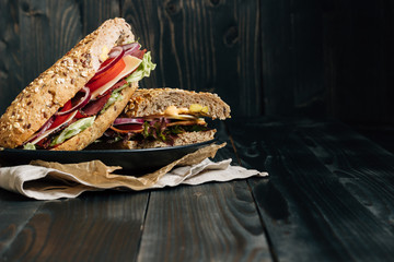 Fresh delicious submarine sandwich on the wooden dark table, with copy space
