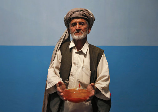 Kabir holds a bowl of shorba, an Afghan soup made from beef or lamb, which is served with bread and potatoes as he poses for a photograph in Kabul