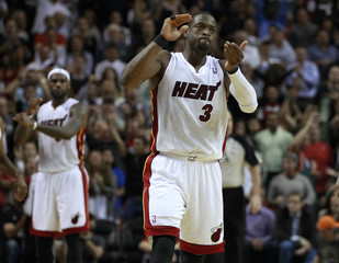 Miami Heat's James and teammate Wade celebrate in the final seconds of the fourth quarter against Indiana Pacers in NBA basketball action in Miami