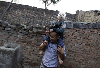 Wang Gengxiang, known as Masked Boy, smiles as he plays with his father Wang Shouwu in the front courtyard of their house at Mijiazhuang village