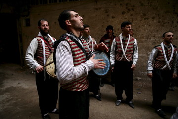 Men, wearing traditional costumes, play music during a wedding ceremony in the rebel held besieged town of Kafr Batna, on the outskirts of Damascus