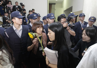 Protester holds a sunflower as she leaves Taiwan's parliament, while police officers stand guard, in Taipei