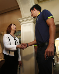 Australian cricketer Starc towers over Australia's PM Gillard as she greets him for afternoon tea at Kirribilli House in Sydney