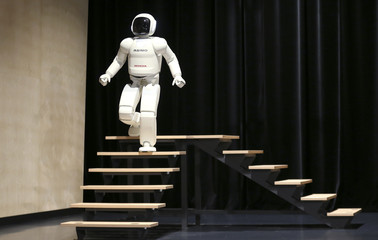 Honda's latest version of the Asimo humanoid robot walks down stairs during a presentation in Zaventem near Brussels