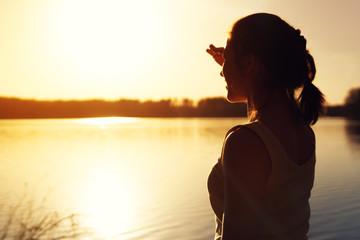 Silhouette of young woman watching sunset nature