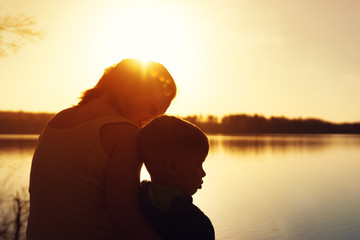 Mother and her son watching sunset outdoors
