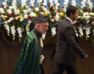 Afghan President Hamid Karzai gestures after his speech at the closing ceremony of a Loya Jirga, or grand assembly, in Kabul