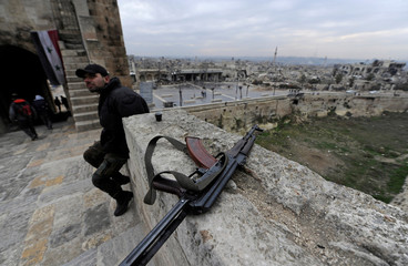 A Syrian army soldier sits near his weapon at Aleppo's historic citadel, in the Old City of Aleppo