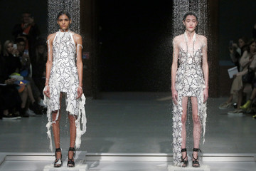 Water falls on models as they present creations by designer Hussein Chalayan as part of his Spring/Summer 2016 women's ready-to-wear collection show during the Fashion Week in Paris