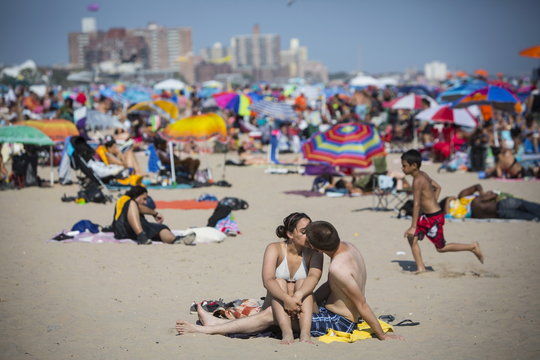 A man and woman kiss on the beach at Coney Island Beach in Brooklyn, New York