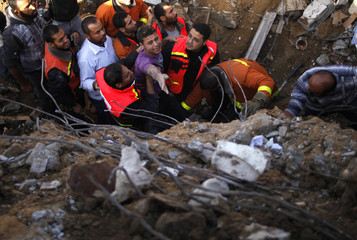 Palestinian members of the Civil Defense help a survivor after he was pulled out from under the rubble of his destroyed house after an Israeli air strike in Gaza City