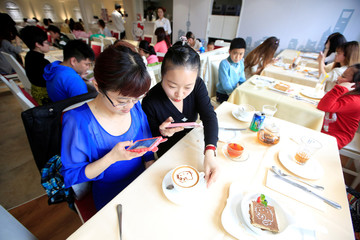Customers take pictures of a cup of coffee in China's first official Hello Kitty-themed restaurant in Shanghai