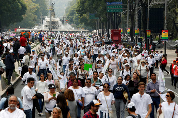 People dressed in white arrive to participate in a march against the legalization of gay marriage and to defend their interpretation of traditional family values near the Angel of Independence monument in Mexico City