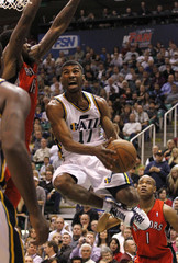 Utah Jazz point guard Ronnie Price drives between Toronto Raptors power forward Amir Johnson and Toronto Raptors point guard Jarrett Jack during the second half of their NBA basketball game in Salt Lake City, Utah