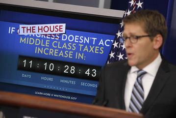 White House Press Secretary Jay Carney is pictured alongside a payroll tax cut extension countdown monitor in the briefing room of the White House in Washington