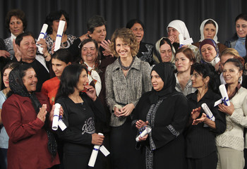 Asma al-Assad, wife of Syrian President Bashar al-Assad, poses with graduates of a government programme to eradicate illiteracy in the Syrian port city of Tartous