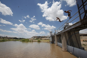 Two men jump to into the Rio Bravo to cool off during a hot summer day at the border crossing  between Mexico and the United States in Ciudad Juarez